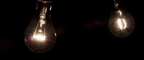 duas lâmpadas clássicas brilhando e balançando na escuridão em 4k