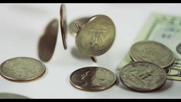 muitas moedas de quarto de dólar caindo sobre duas moedas e uma nota de $ 20 na mesa branca, finalmente oito moedas e a nota colocada na cena em 4k