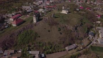 Drone flying towards an old castle ruins and a church in 4K