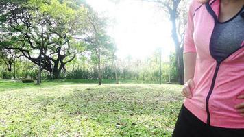 mulher asiática jovem saudável exercitando no parque. cabe jovem fazendo treinamento comout na manhã.