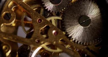 Extreme close up of pocket watch machinery with small gears spinning in 4K video