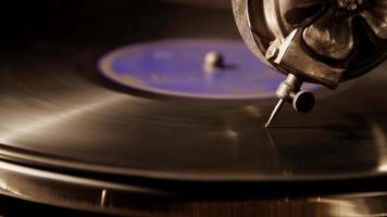 Cena de close-up escuro extremo da agulha reprodutora em disco de vinil antigo com etiqueta roxa em 4k