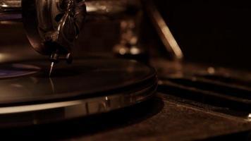escuro extremo close-up de agulha decorada tocando um disco de vinil em dispositivo de música vintage iluminação suave no teto em 4k