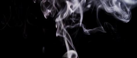espirales de humo blanco girando y creando olas que suben en un fondo de corteza oscuro en 4k