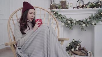 Hermosa mujer asiática atractiva sosteniendo una taza de café o té caliente mientras está acostado en una silla cuando se relaja en su sala de estar en casa.