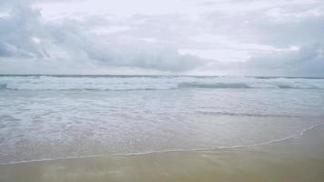 Landschaft des tropischen Sandstrandes mit Schaum, der durch Wellen in Phuket, Thailand gebildet wird. video