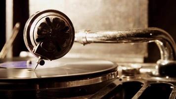 Extreme Nahaufnahme von Plattenspielernadel und Vinylscheibe, die sich mit hellem Wenig von der linken Seite in 4k drehen