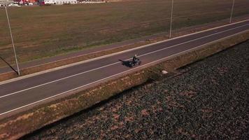 drone segue uma motocicleta do perfil direito traseiro em 4k