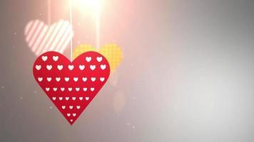 Corazones de San Valentín de papel cayendo colgando de una cadena de fondo blanco.