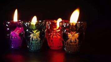 cuatro contenedores de calaveras con velas
