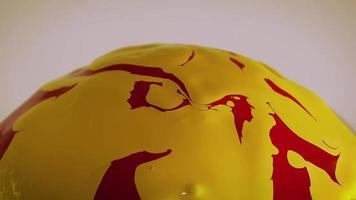 Pintura roja y amarilla sobre esfera de cristal.
