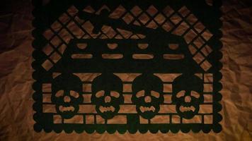 papel picoteado tradicional de cuatro calaveras y un ataúd
