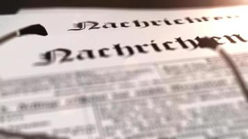 glasses with newspaper with the headline Nachrichten - german word for news - on a table