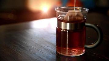 se vierte el té en una taza de té de vidrio