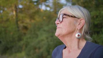 Cerca de la anciana respirando profundamente con árboles en segundo plano.