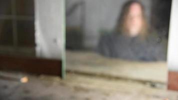 Hombre deprimido y enojado sentado frente a su reflejo borroso