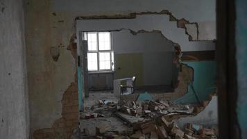Hombre deprimido y loco lanza una puerta a través de una habitación en una vieja casa abandonada