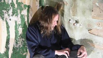 homem deprimido e zangado está sentado no canto de uma casa abandonada video