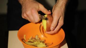 mãos descascando batatas video