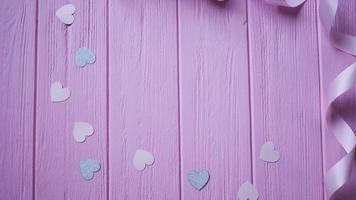 fita e confetes em um fundo rosa de madeira