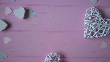 corações e confetes em um fundo rosa de madeira