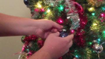 um enfeite sendo colocado em um galho de uma árvore de natal video