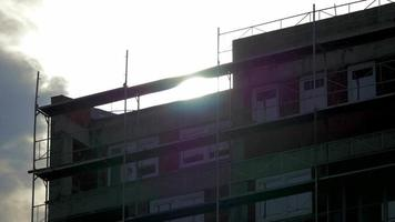 tiro de un edificio sin terminar a través de los rayos del sol 4k stock video