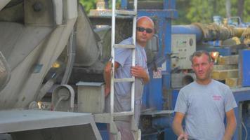 Los visitantes de la construcción y un camión de cemento 4k stock video