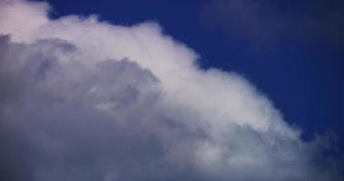 Time lapse of cumulus clouds spinning and disappearing on blue sky in 4K