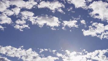 lapso de tempo de nuvens altocumulus movendo-se no céu azul e a luz do sol brilha na parte inferior da cena em 4k