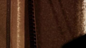 close up de um projetor de filme 8mm, mostrando o filme movendo-se verticalmente de baixo para cima e projetando-se na sombra da bobina em 4k video
