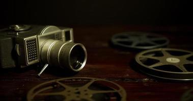 Toma panorámica en la superficie oscura de los carretes, la cámara y las bandas de película que se mueven en 4k