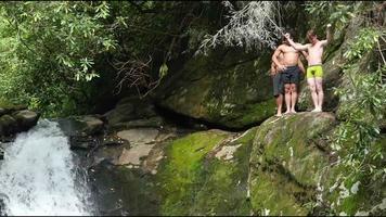 precipício homens jovens pulando de uma cachoeira | filme de arquivo grátis