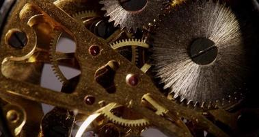 Extreme close up of pocket watch machinery with golden gears in 4K video