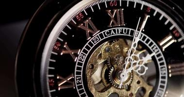 Extreme close up of pocket watch with exposed machinery coming for twenty four minutes in 4K time lapse video