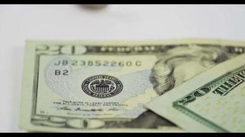 um monte de moedas de um quarto de dólar caindo sobre duas notas de $ 20 na mesa branca, finalmente duas moedas e ambas as notas colocadas na cena em 4k