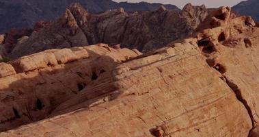foto panorâmica vertical subindo mostrando lindas pedras vermelhas com saturação diferente na paisagem do deserto com montanhas ao fundo em 4k