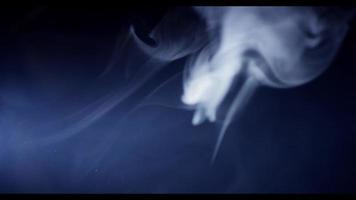 Soft white smoke defocused in foreground, focused in background and disappearing in darkness in 4K video
