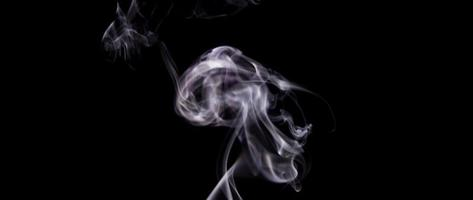 Blurred and focused focal points of soft white smoke floating in darkness in 4K video