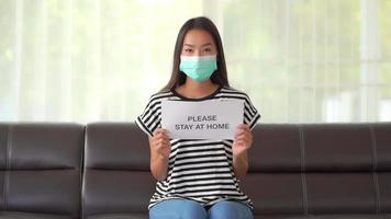 Young asian woman wearing a mask and holding a sign video