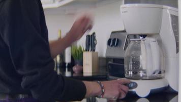 junge Frau beginnt die Kaffeemaschine