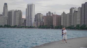 Pareja tomando fotografías de la ciudad de Chicago desde un muelle
