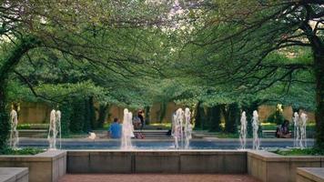 pessoas em um belo parque público com árvores e fonte