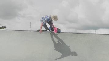 Disparo de ángulo bajo de joven subiendo una rampa y cayendo