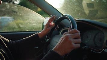 Cerca de anciana conduciendo y fumando