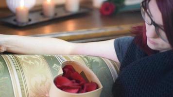 Valentinstag Geschenk. junges Mädchen, das Herzgeschenkbox mit Rosenblättern öffnet video