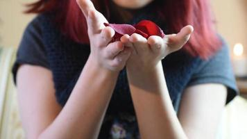 regalo de San Valentín. niña soplando pétalos de rosa hacia la cámara video