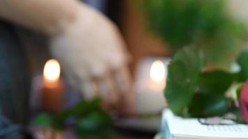 Cerrar recogiendo una rosa roja de la mesa con libro y velas