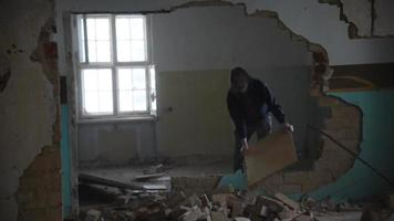 Hombre deprimido y loco arroja una tabla al suelo en una casa abandonada