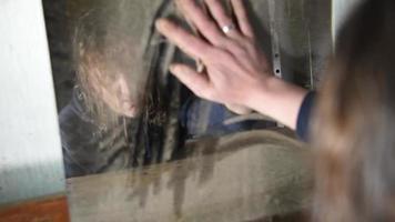 Hombre deprimido y enojado limpia su mano sobre un espejo sucio en una vieja casa abandonada